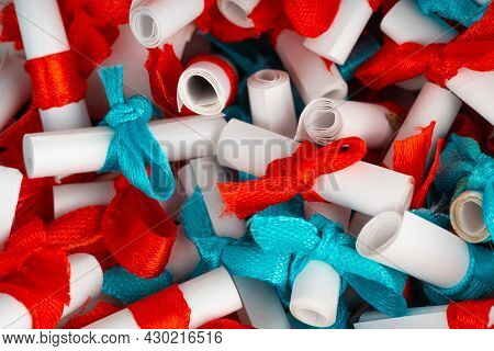 Close Up Of Small Rolled Notes Into Tubes With Wishes. Texture Of Small Pieces Of Paper Rolled Up An