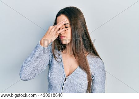 Young brunette teenager wearing casual sweater and glasses tired rubbing nose and eyes feeling fatigue and headache. stress and frustration concept.