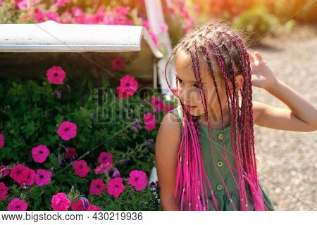 A Beautiful Cute Girl With Pink Afro-pigtails From Kanekalon Stands In Front Of A Flower Bed With Fl