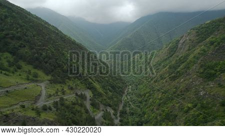 Beautiful Mountain Valley With Greenery And Cloudy Sky. Action. Top View Of Mountain Landscape With