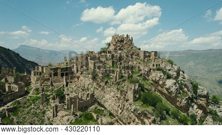 Ancient Stone City On Rock On Background Of Mountains. Action. Amazing Settlement Of Rock Houses On