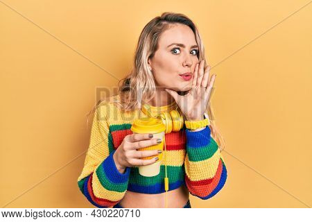 Beautiful young blonde woman drinking cup of coffee wearing headphones hand on mouth telling secret rumor, whispering malicious talk conversation