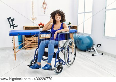 Young middle eastern woman sitting on wheelchair at physiotherapy clinic doing happy thumbs up gesture with hand. approving expression looking at the camera showing success.