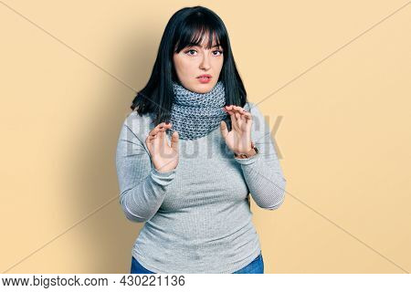 Young hispanic plus size woman wearing winter scarf moving away hands palms showing refusal and denial with afraid and disgusting expression. stop and forbidden.