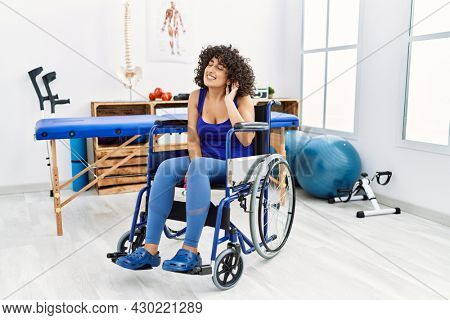 Young middle eastern woman sitting on wheelchair at physiotherapy clinic smiling with hand over ear listening an hearing to rumor or gossip. deafness concept.