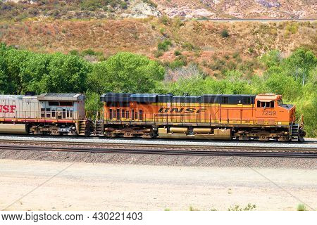 August 17, 2021 In Cajon Junction, Ca:  Locomotive Pulling Freight Cars Surrounded By Arid Badlands