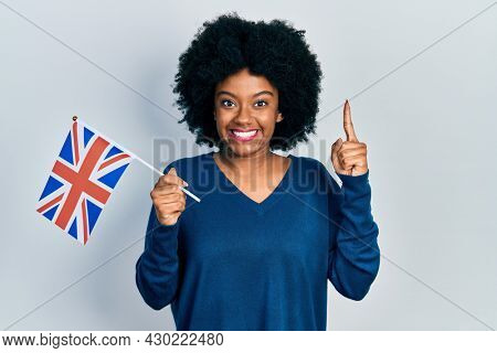 Young african american woman holding united kingdom flag smiling with an idea or question pointing finger with happy face, number one