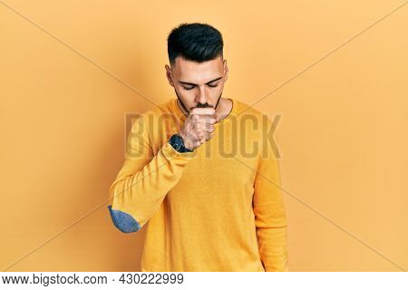 Young hispanic man with beard wearing casual winter sweater feeling unwell and coughing as symptom for cold or bronchitis. health care concept.