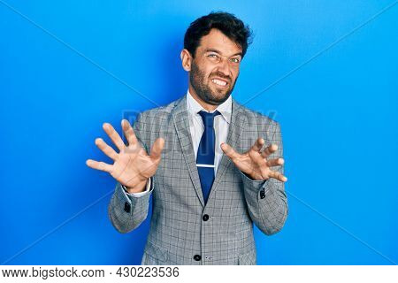 Handsome man with beard wearing business suit and tie disgusted expression, displeased and fearful doing disgust face because aversion reaction. with hands raised