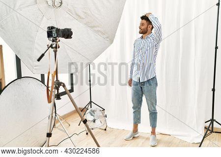Arab young man posing as model at photography studio smiling confident touching hair with hand up gesture, posing attractive and fashionable