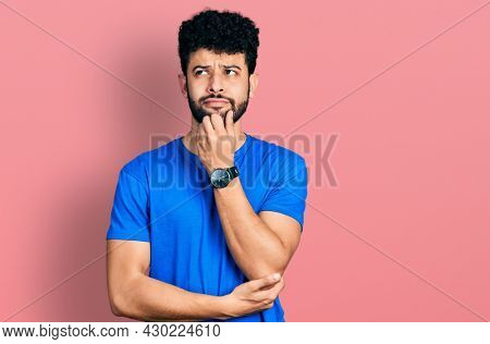 Young arab man with beard wearing casual blue t shirt with hand on chin thinking about question, pensive expression. smiling and thoughtful face. doubt concept.
