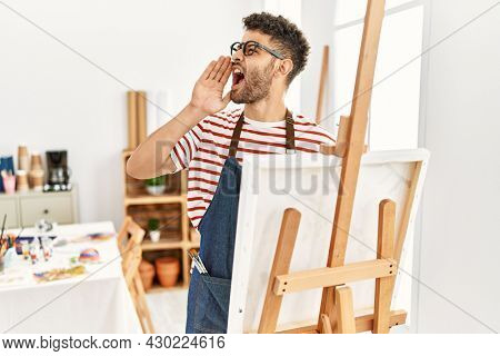 Arab young man at art studio shouting and screaming loud to side with hand on mouth. communication concept.