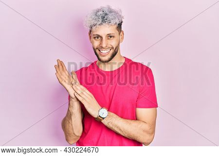 Young hispanic man with modern dyed hair wearing casual pink t shirt clapping and applauding happy and joyful, smiling proud hands together