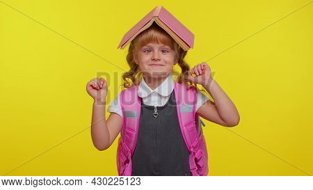 Cheerful Funny Teenage Schoolgirl Kid Dressed In Uniform Posing With Book On Head Looking Happy Maki
