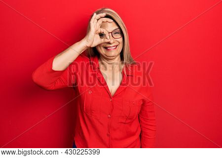 Middle age hispanic woman wearing casual clothes and glasses smiling happy doing ok sign with hand on eye looking through fingers