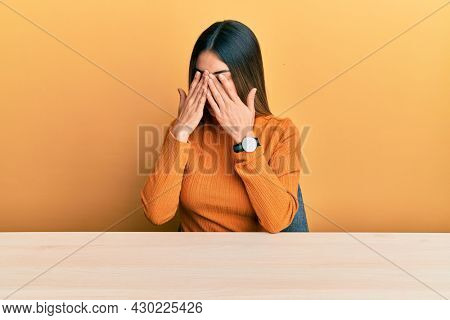Young hispanic woman wearing casual clothes sitting on the table rubbing eyes for fatigue and headache, sleepy and tired expression. vision problem