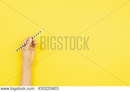Left Hand Holding Pencil For Writing Over Yellow Background. Top View, Copy Space For Text. Left Han