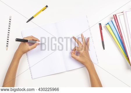 Kid Holding Pencil In Left Hand For Writing In Notebook, Doing Homework. Hand Gesture Sign Ok, Okay,