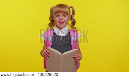 Smiling Schoolgirl Wears Backpack, Holding A Book, Laugh Fooling Around Showing Tongue Making Playfu