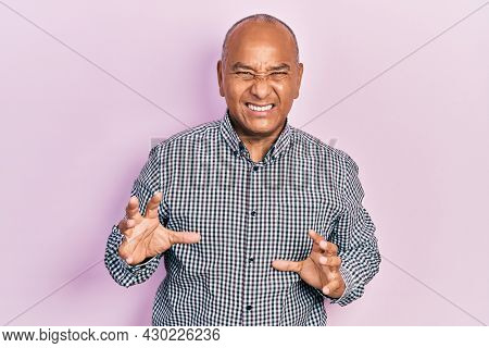Middle age latin man wearing casual clothes disgusted expression, displeased and fearful doing disgust face because aversion reaction. with hands raised