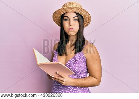 Young brunette woman reading book puffing cheeks with funny face. mouth inflated with air, catching air.