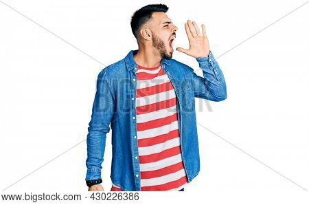 Young hispanic man with beard wearing casual denim jacket shouting and screaming loud to side with hand on mouth. communication concept.
