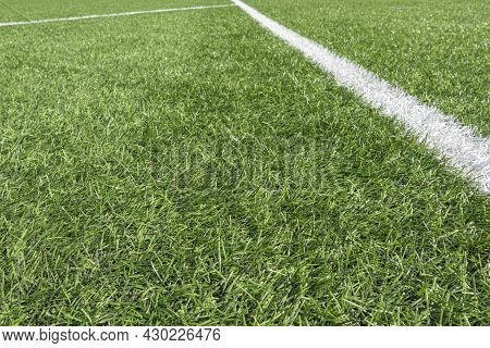 Soccer Football Background. Green Synthetic Artificial Grass Soccer Sports Field With White Stripe L