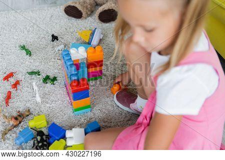 Blurred Girl In Pink Dress Playing Building Blocks On Carpet In Kindergarten Playroom