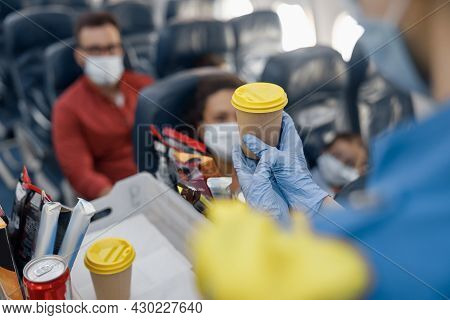 Close Up Shot Of Hands In Protective Gloves Of Flight Attendant Serving Drinks To Passengers On Boar