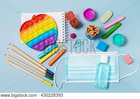 School Supplies, Poppit Anti-stress, Face Mask, Bottle Of Sanitizer, For Back To School On A Blue Ba