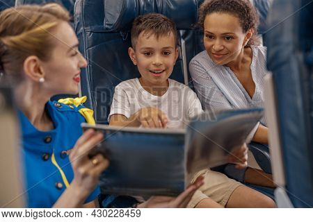 Female Flight Attendant Entertaining A Kid On Board By Offering A Book To Read. Cabin Crew Provide S