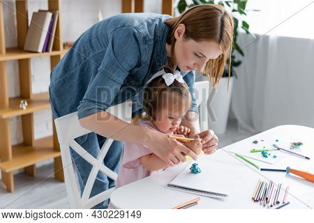 Teacher Assisting Disabled Child With Down Syndrome Molding Plasticine In Private Kindergarten