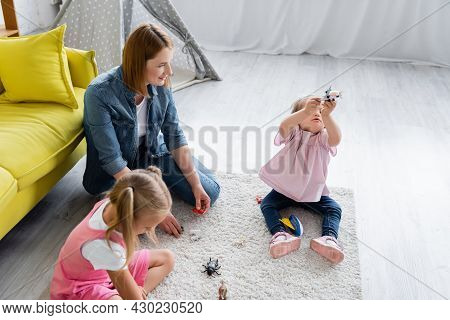 High Angle View Of Kindergarten Teacher Looking At Toddler Girl With Down Syndrome Playing With Toy