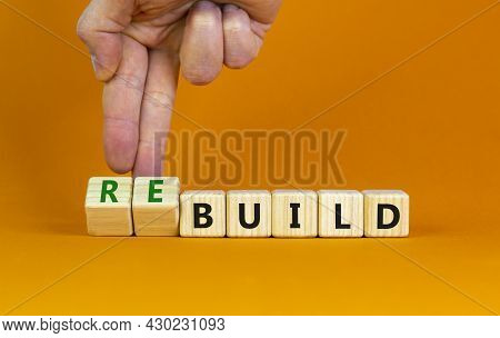 Time To Rebuild. Businessman Turns Wooden Cubes And Changes The Word Build To Rebuild On A Beautiful