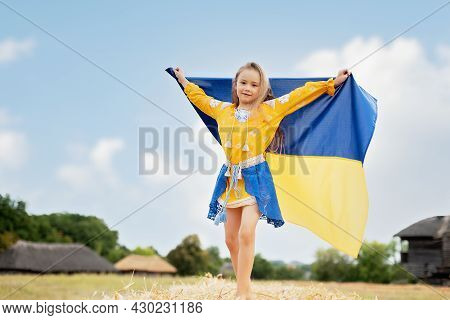 Ukrainian Child Girl In Embroidered Shirt Vyshyvanka With Yellow And Blue Flag Of Ukraine In Field.