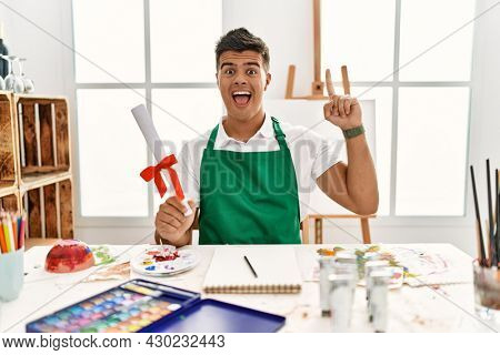 Young hispanic man at art studio holding degree smiling amazed and surprised and pointing up with fingers and raised arms.