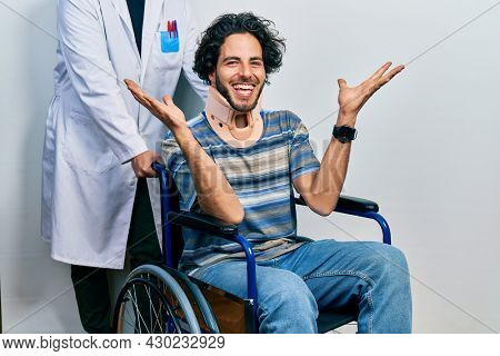 Handsome hispanic man sitting on wheelchair wearing neck collar celebrating crazy and amazed for success with arms raised and open eyes screaming excited. winner concept