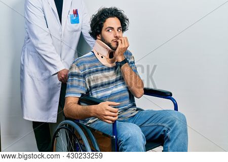 Handsome hispanic man sitting on wheelchair wearing neck collar looking stressed and nervous with hands on mouth biting nails. anxiety problem.