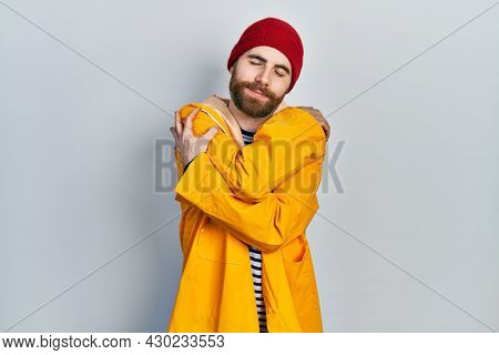 Caucasian man with beard wearing yellow raincoat hugging oneself happy and positive, smiling confident. self love and self care