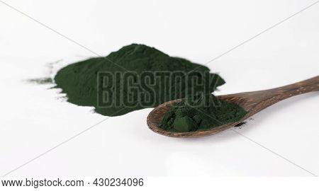 Organic Spirulina Algae Powder In Wooden Spoon On White Background.