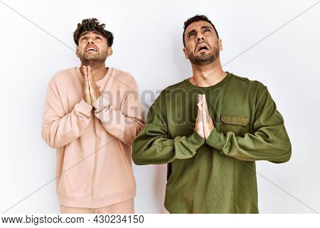 Young gay couple standing over isolated white background begging and praying with hands together with hope expression on face very emotional and worried. begging.