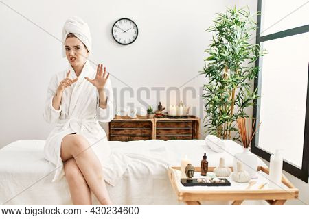 Young blonde woman wearing bathrobe at wellbeing spa disgusted expression, displeased and fearful doing disgust face because aversion reaction. with hands raised