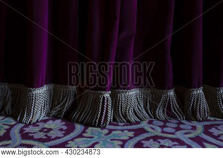 Folds And Fringe Of A Burgundy Colored Velvet Curtain In An Old Theater
