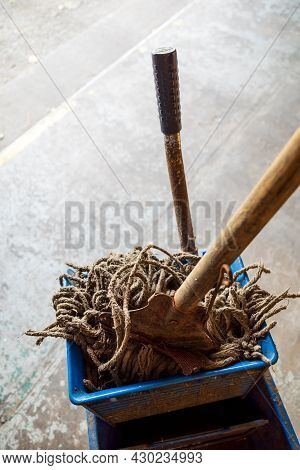 Old Mop With Wooden Handle And Blue Mop Bucket