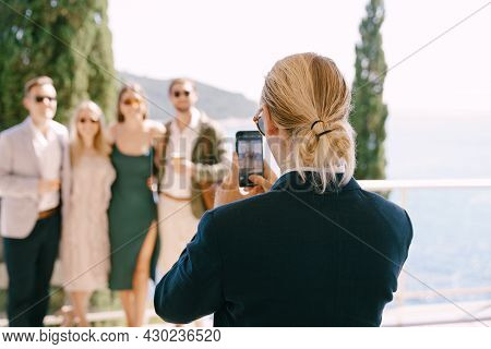 Man In A Suit Shoots A Group Of People On A Smartphone Against The Background Of The Sea