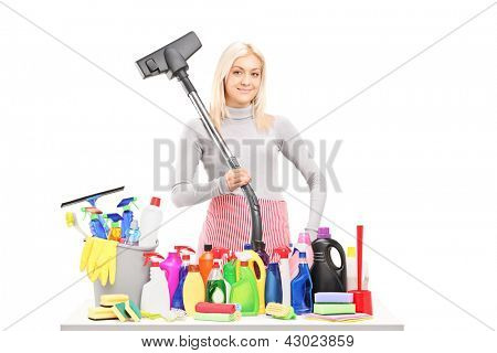 Young smiling woman with a hover and cleaning supplies on a table