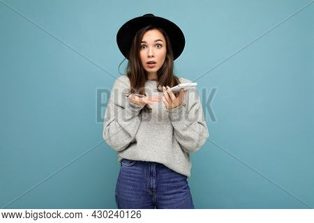 Beautiful Young Asking Dissatisfied Brunette Woman Wearing Black Hat And Grey Sweater Holding Smartp