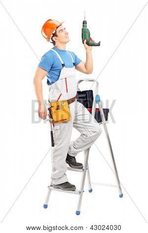 Un joven trabajador en una escalera con una taladradora aislada sobre fondo blanco