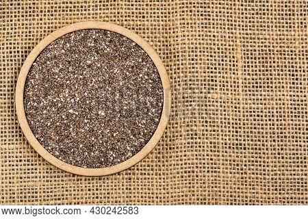 Dried Organic Chia Seeds On Burlap Background - Salvia Hispanica