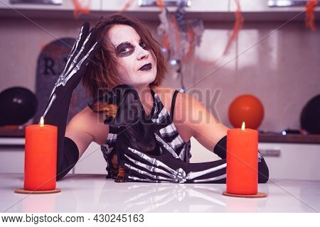 Woman Wearing Skeleton Costume With Scary Festive Makeup Adorable Dachshund Dog In Kitchen Decorated